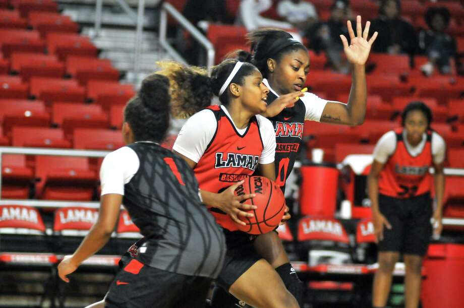 Lamar's Ashlan Miles, right, splits between Jadyn Pimentel, foreground, and Lola Bracy as the Red and Black team scrimmage to kick off Tuesday's Big Red Madness event at the Montagne Center. (Mike Tobias/The Enterprise) Photo: Mike Tobias/The Enterprise