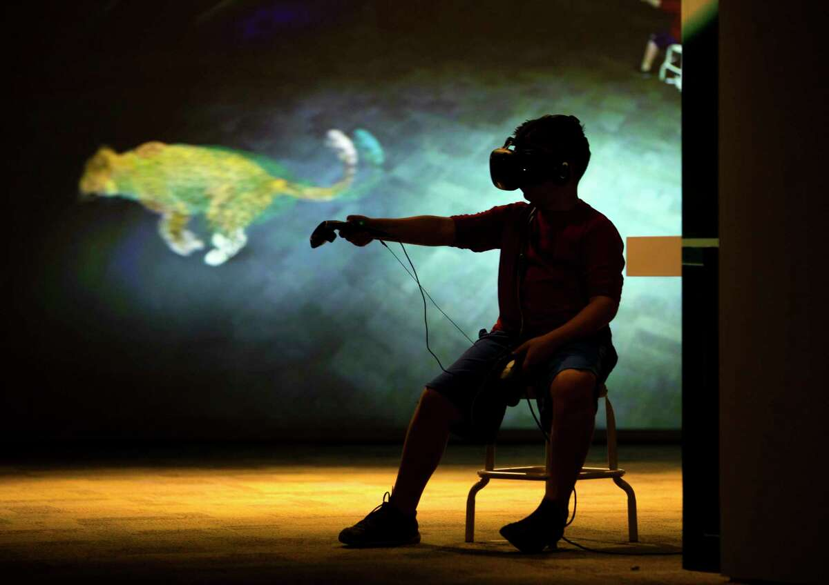 Mateo Bernal plays one of the virtual reality games in the Reality Check exhibit at the Houston Museum of Natural Science.