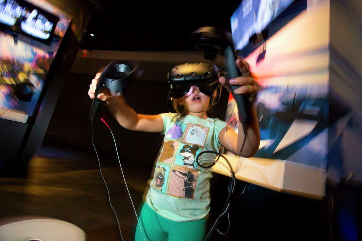 Karen Garcia, 4, plays a virtual reality game in the Reality Check exhibit at the Houston Museum of Natural Science.
