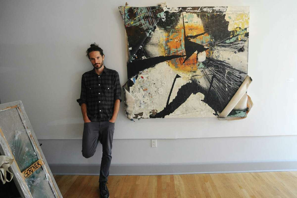Artist James Gortner poses beside one of his pieces inside the Fernando Luis Alvarez Gallery on Bedford Street in downtown Stamford, Conn. on Monday, Oct. 23, 2017.