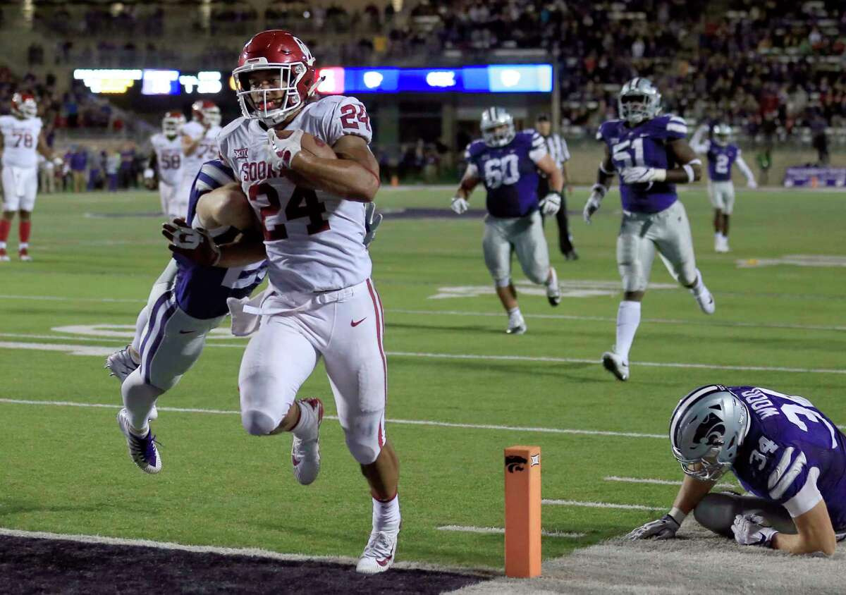 Oklahoma running back Rodney Anderson (24) scores a touchdown past Kansas State defensive back Sean Newlan (29) and Kansas State defensive end Tanner Wood (34) during the second half of an NCAA college football game in Manhattan, Kan., Saturday, Oct. 21, 2017. Oklahoma defeated Kansas State 42-35. (AP Photo/Orlin Wagner)