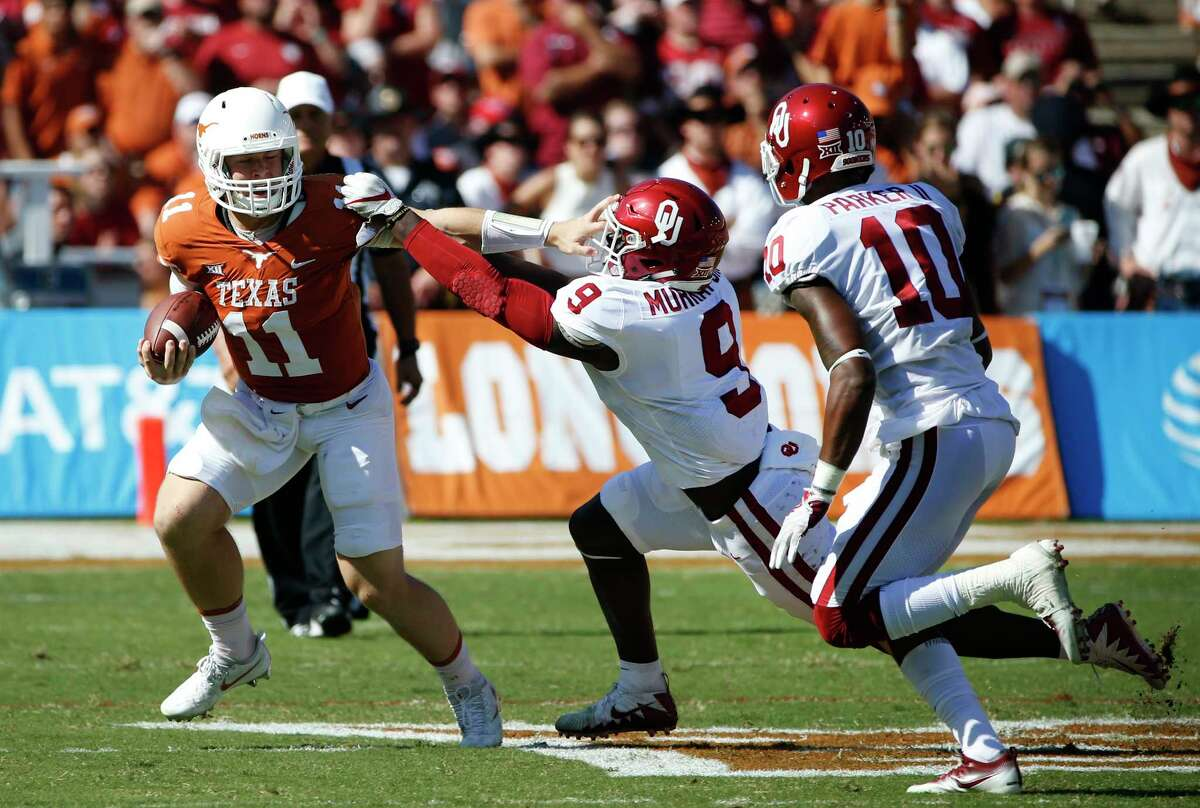 Texas quarterback Sam Ehlinger (11) tries to get past Oklahoma linebacker Kenneth Murray (9) and cornerback Parnell Motley (11) during the first half of an NCAA college football game Saturday, Oct. 14, 2017, in Dallas. (AP Photo/Ron Jenkins)