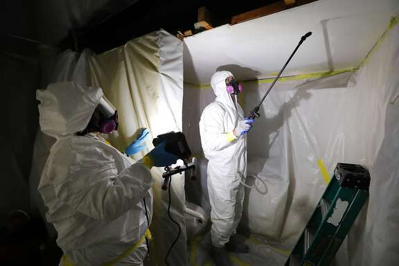 CORRECTS DATE TO OCT. 18, 2017 FROM JULY 12, 2017 - In this Oct. 18, 2017, photo, Asbestos Removal Technologies Inc., job superintendent Ryan Laitila, right, sprays amended water as job forman Megan Eberhart holds a light during asbestos abatement in Howell, Mich. Asbestos fibers can become deadly when disturbed in a fire or during remodeling, lodging in the lungs and causing problems including mesothelioma, a form of cancer. The material�s dangers have long been recognized. But a 1989 attempt to ban most asbestos products was overturned by a federal court, and it remains in widespread use. (AP Photo/Paul Sancya)