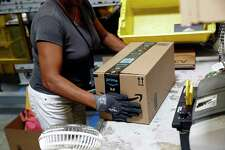 ADVANCE FOR SUNDAY, OCT. 29, 2017, AND THEREAFTER - In this Aug. 3, 2017, photo, Myrtice Harris applies tape to a package before shipment at an Amazon fulfillment center in Baltimore. While jobs have been lost in brick-and-mortar stores, many more have been gained from e-commerce and warehousing. Amazon accounts for much of the additional employment.
