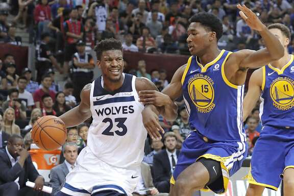 Minnesota Timberwolves' Jimmy Butler, left, drives past Golden State Warriors' Damian Jones during the basketball match of the 2017 NBA Global Games in Shenzhen, south China's Guangdong province, Thursday, Oct. 5, 2017. (AP Photo/Kin Cheung)