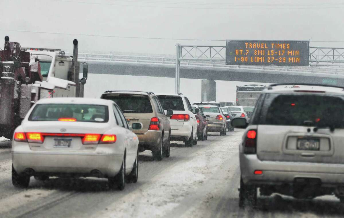 An optimistic road sign and traffic bogged down in the south bound lanes of the Northway by a snow storm Friday morning Feb. 25, 2011. (John Carl D'Annibale / Times Union)