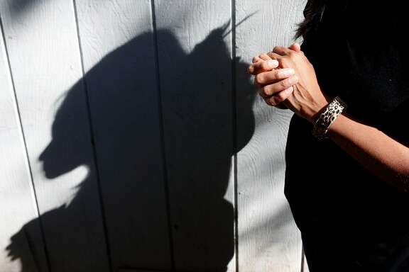 Alicia, who doesn't to reveal her last name, casts a shadow at a family member's home in Sonoma, Calif. on Wednesday Oct. 25, 2017. Many undocumented residents affected by the wildfires are reluctant to file for FEMA claims fearing their status may be passed on to the Department of Homeland Security.
