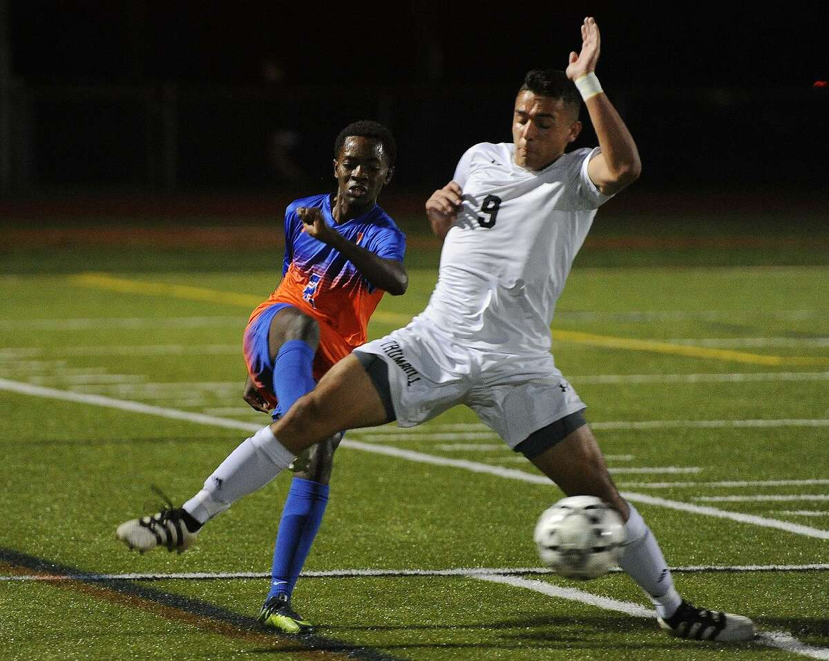 Danbury's Brandon Tyndale, left, passes the ball defended by Trumbull's Jason Weinstein during their boys soccer game at Trumbull High School in Trumbull, Conn. on Monday, October 23, 2017.