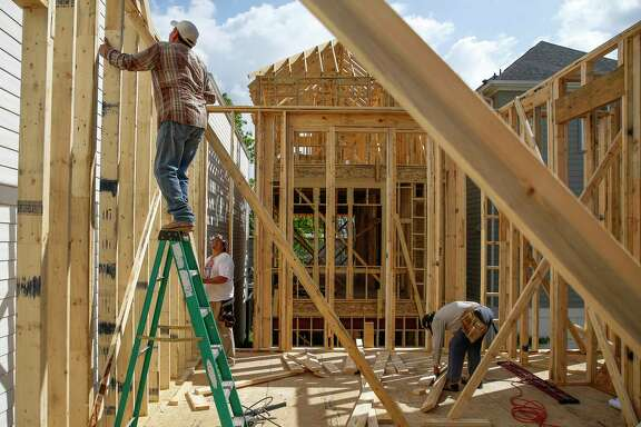 Immigrant construction workers build a house off West 23rd Street in Houston earlier this year. ( Michael Ciaglo / Houston Chronicle )