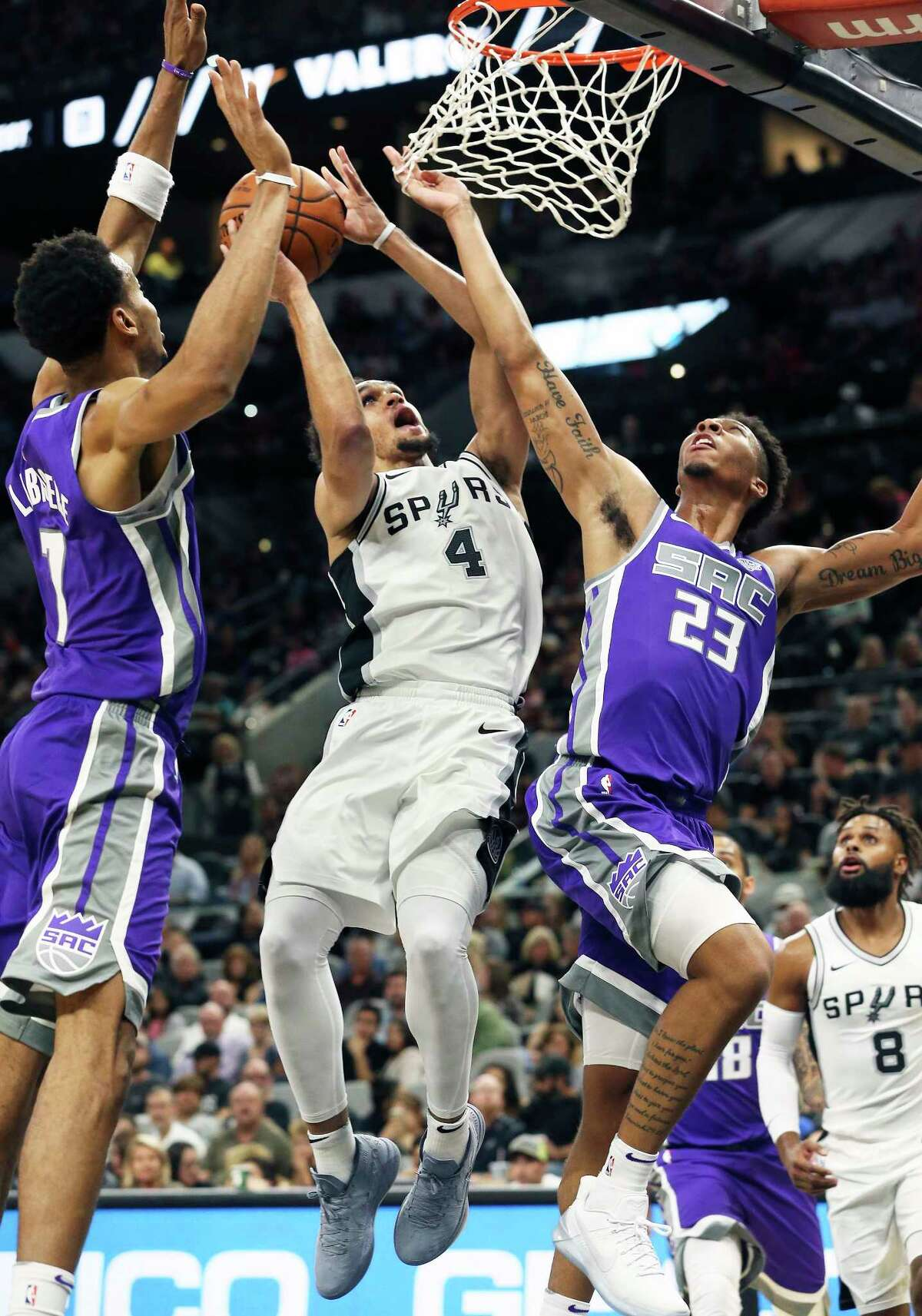 Derrick White gets to the basket through the defense of Skal Labissiere and Malachi Richardson (23) as the Spurs play the Kings at the AT&T Center on October 6, 2017.
