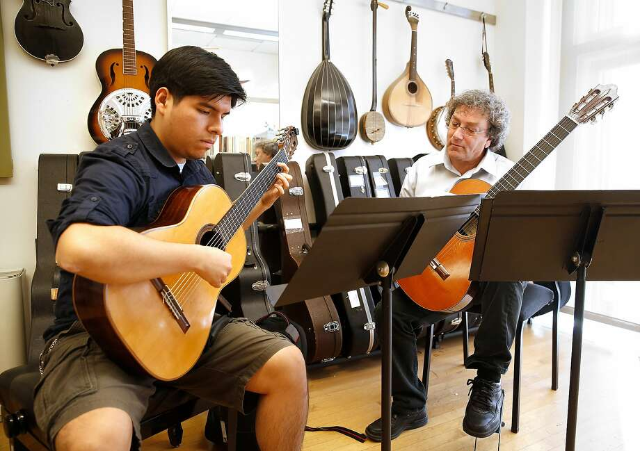 Guitar ensemble director David Tanenbaum (right) instructs Gianfraco Baltazar. Tanenbaum began teaching at the conservatory in 1982 and was later appointed department chair. Photo: Liz Hafalia, The Chronicle