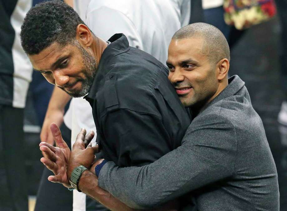 Tony Parker comes up from behind and hugs Tim Duncan who was on the court during pre game ceremonies as the Spurs play Minnesota in the season opener at the AT&T Center on October 18, 2017. Photo: Tom Reel, San Antonio Express-News / 2017 SAN ANTONIO EXPRESS-NEWS