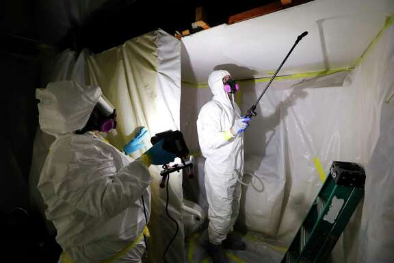 In this July 12, 2017, photo, Asbestos Removal Technologies Inc., job superintendent Ryan Laitila, right, sprays amended water as job forman Megan Eberhart holds a light during asbestos abatement in Howell, Mich. Asbestos fibers can become deadly when disturbed in a fire or during remodeling, lodging in the lungs and causing problems including mesothelioma, a form of cancer. The material's dangers have long been recognized. But a 1989 attempt to ban most asbestos products was overturned by a federal court, and it remains in widespread use. (AP Photo/Paul Sancya)