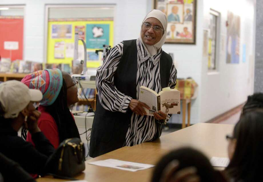 "N.Y. Nathiri holds a copy of Zora Neale Hurston's novel ""Mules and Men"" while speaking with children at Davis Middle School. Nathiri, like Hurston, grew up in Eatonville, Fla. Photo: Billy Calzada / San Antonio Express-News"