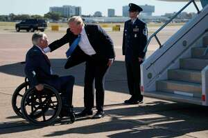 US President Donald Trump (C) speaks with Texas Governor Greg Abbott (L) as he arrives at Dallas Love Field in Dallas, Texas, on October 25, 2017. / AFP PHOTO / JIM WATSONJIM WATSON/AFP/Getty Images