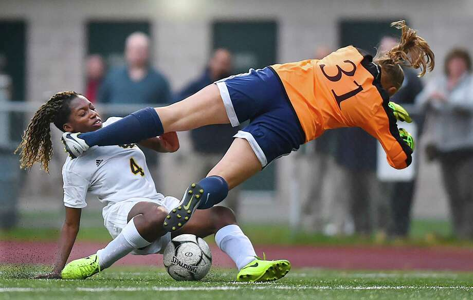 Law senior Rhea Grant collides with Foran junior goalkeeper in the second half in crosstown battle, Wednesday, Oct. 25, 2017, at Jonathan Law High School in Milford. The match ended in a 2-2 tie. Photo: Catherine Avalone, Hearst Connecticut Media / New Haven Register