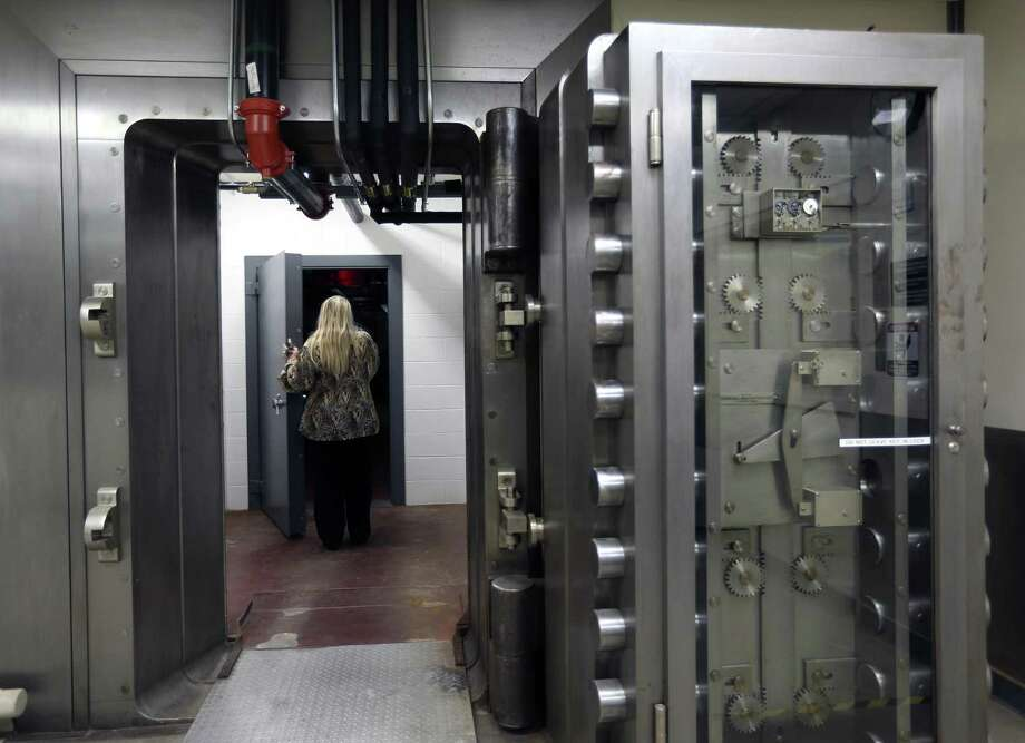 Leslie Stapleton opens a secure door Tuesday in the basement of the former Federal Reserve building in downtown. The building is now the home of the Daughters of the Republic of Texas library collection through an agreement with Texas A&M University - San Antonio and Bexar County, which owns the building. Photo: William Luther /San Antonio Express-News / © 2017 San Antonio Express-News