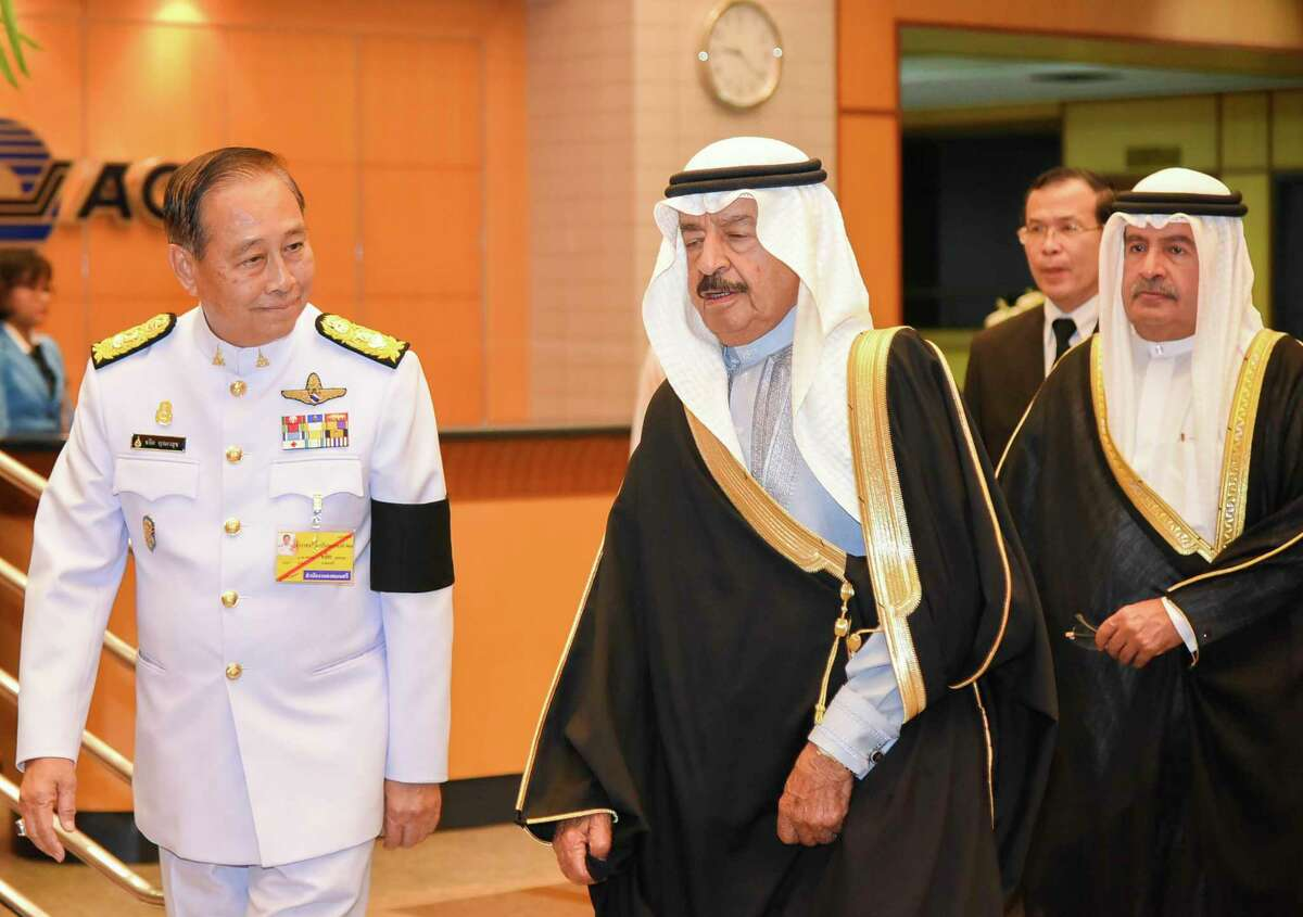In this Oct. 21, 2017, photo, Bahrain's Prince Khalifa bin Salman Al Khalifa is greeted by Air Chief Marshal Chalit Pookpasuk as he arrives to attend the Royal Cremation Ceremony the late Thai King Bhumibol Adulyadej, in Bangkok, Thailand. (Thailand Ministry of Foreign Affairs via AP)