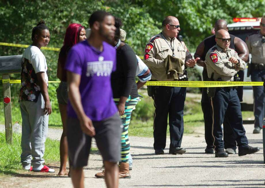 Residents walk near Deputies with the Montgomery County Sherriff's Office as they investigate the scene of a shooting that left two men dead on Bimms Drive in the historic community of Tamina near The Woodlands, Thursday, July 20, 2017. Jaquise Williams, 23, and Akeen Russell, 24, were found dead of apparent gunshot wounds in a home near Simmons Drive and Bimms Drive. Photo: Jason Fochtman, Staff Photographer / © 2017 Houston Chronicle
