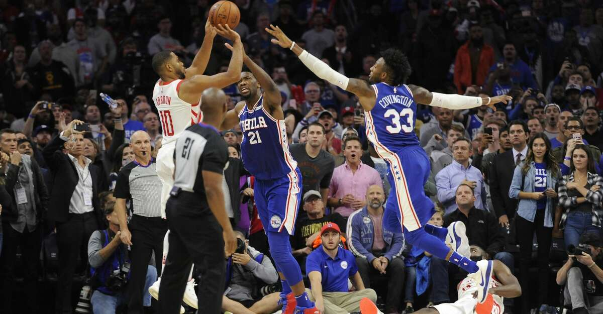 Houston Rockets' Eric Gordon (10) takes a three point shot as Philadelphia 76ers' Joel Embiid (21) and Robert Covington (33) defend in the second half of an NBA basketball game, Wednesday, Oct. 25, 2017, in Philadelphia. The Rockets on 105-104. (AP Photo/Michael Perez)