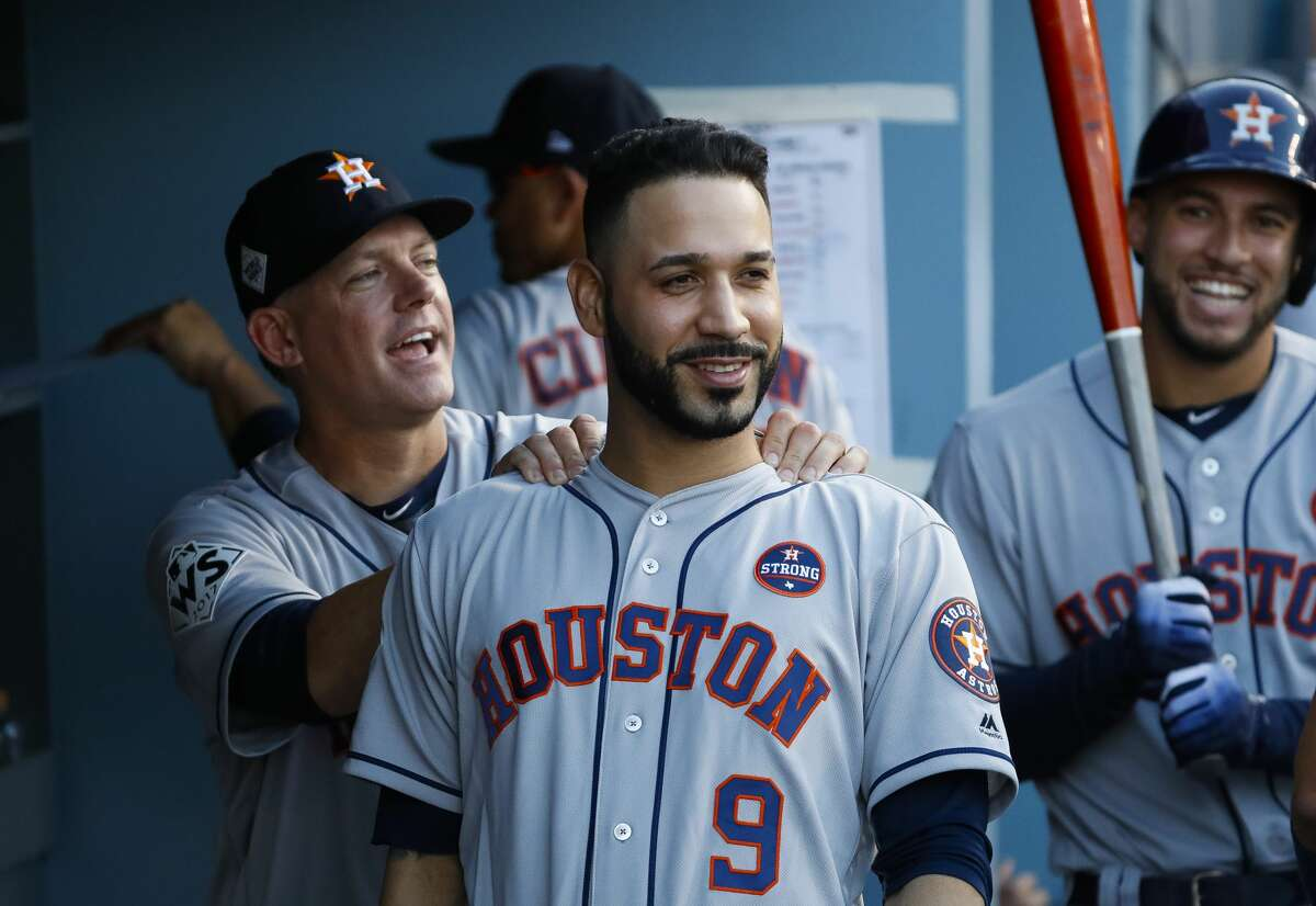 A.J. Hinch jokes with Houston Astros left fielder Marwin Gonzalez (9) before Game 2 of the World Series at Dodger Stadium on Wednesday, Oct. 25, 2017, in Los Angeles.
