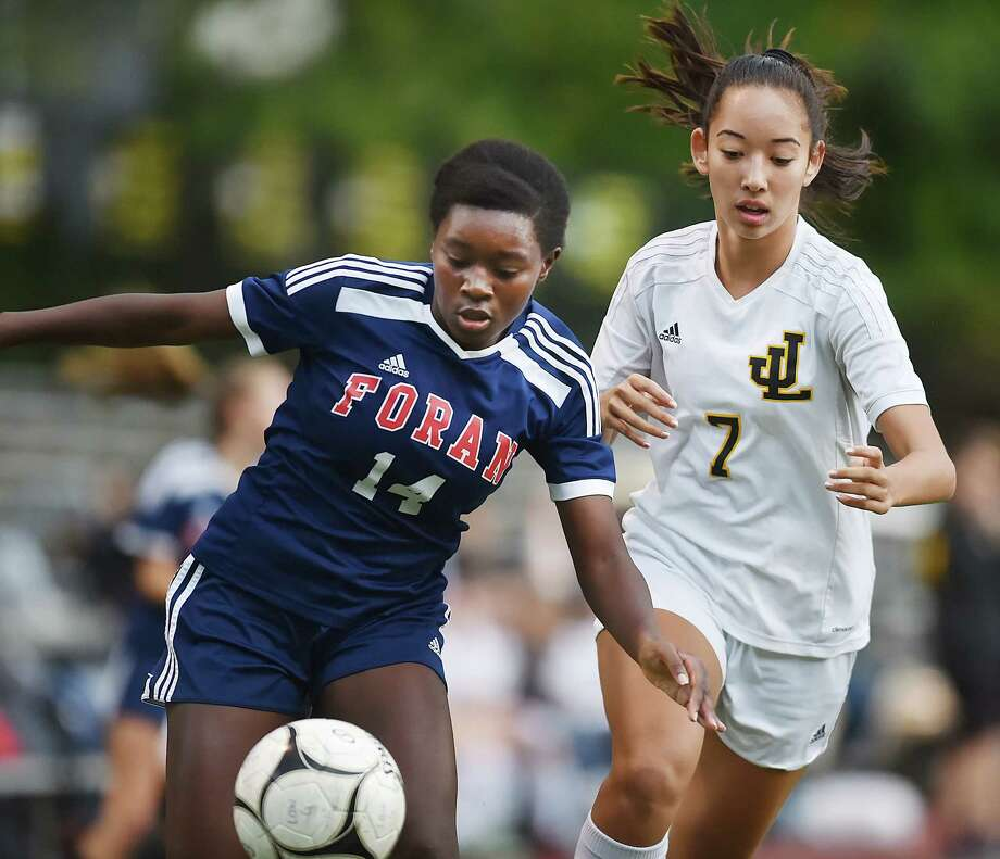 Foran Yasmina Lingane battles Law sophomore Makayla Mai in a crosstown rival match, Wednesday, Oct. 25, 2017, at Lawmen Stadium at Jonathan Law High School in Milford. The game ended in a 2-2 tie. Photo: Catherine Avalone, Hearst Connecticut Media / New Haven Register