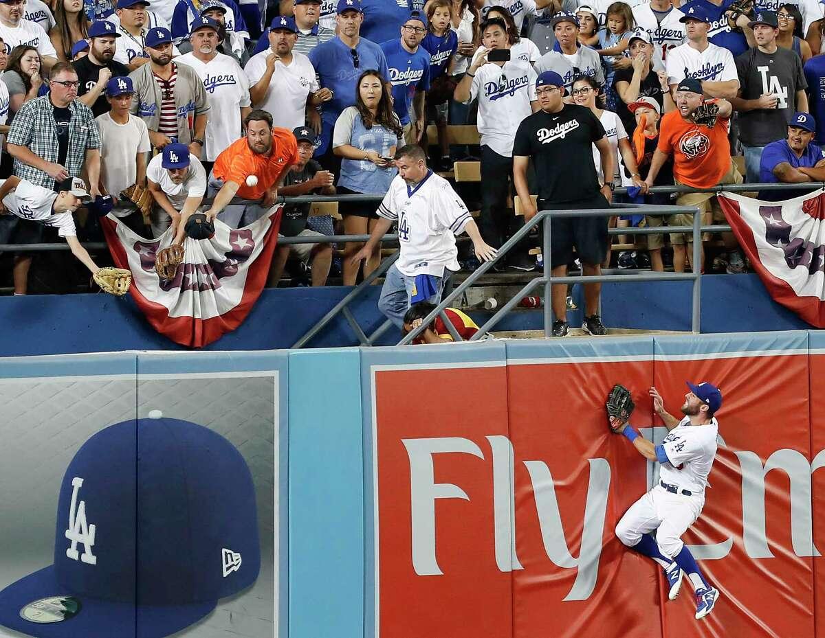 Los Angeles Dodgers center fielder Joc Pederson (31) slams against the outfield wall as a home run hit by Houston Astros left fielder Marwin Gonzalez (9) flies out of the park during the ninth inning of Game 2 of the World Series at Dodger Stadium on Wednesday, Oct. 25, 2017, in Los Angeles.