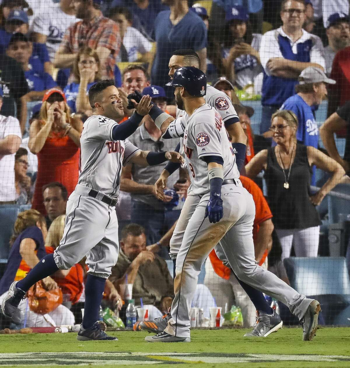 Houston Astros second baseman Jose Altuve (27) and short stop Carlos Correa greet left fielder Marwin Gonzalez (9) at home after Gonzalez hit a home run in the ninth inning of Game 2 of the World Series at Dodger Stadium on Wednesday, Oct. 25, 2017, in Los Angeles.