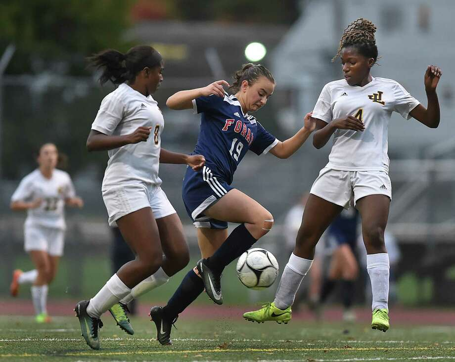 Foran sophomore Sara Portoff battles Law junior forward Samara Thacker (#8) and senior forward Rhea Grant (#4) in a crosstown matchup, Wednesday, Oct. 25, 2017, at Lawmen Stadium at Jonathan Law High School in Milford. The game ended in a 2-2 tie. Photo: Catherine Avalone, Hearst Connecticut Media / New Haven Register