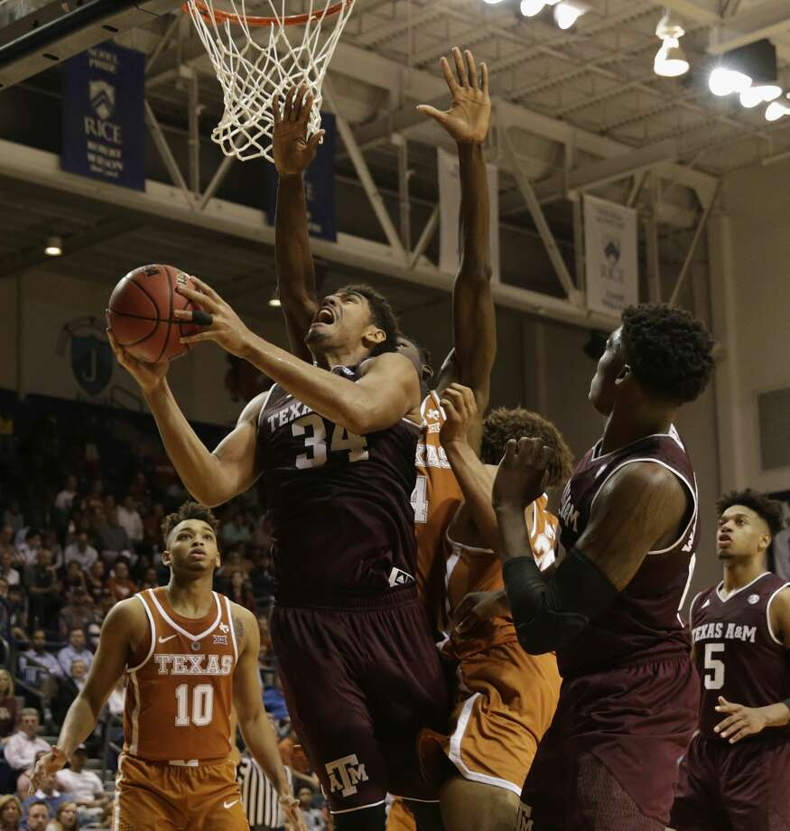 Texas A&M Aggies center Tyler Davis (34) goes up for a shot defended by Texas Longhorns forward Mohamed Bamba (4) in the second half during the exhibition basketball game between the Texas Longhorns and the Texas A&M Aggies to benefit the Rebuild Texas Relief Fund at Tudor Fieldhouse in Houston, TX on Wednesday, October 25, 2017. Photo: Tim Warner/For The Chronicle