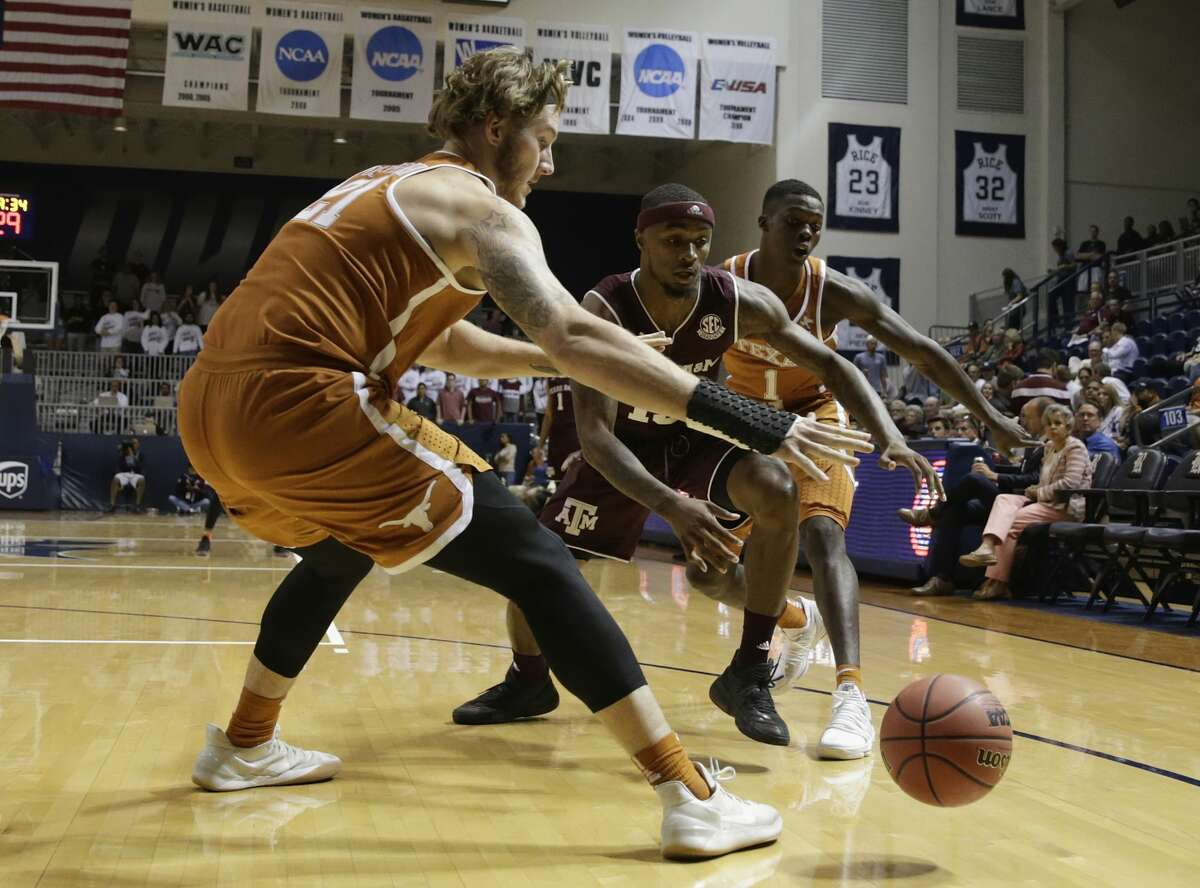 Texas A&M Aggies guard Duane Wilson (13) and Texas Longhorns forward Dylan Osetkowski (21) battle for a loose ball in the first half during the exhibition basketball game between the Texas Longhorns and the Texas A&M Aggies to benefit the Rebuild Texas Relief Fund at Tudor Fieldhouse in Houston, TX on Wednesday, October 25, 2017.
