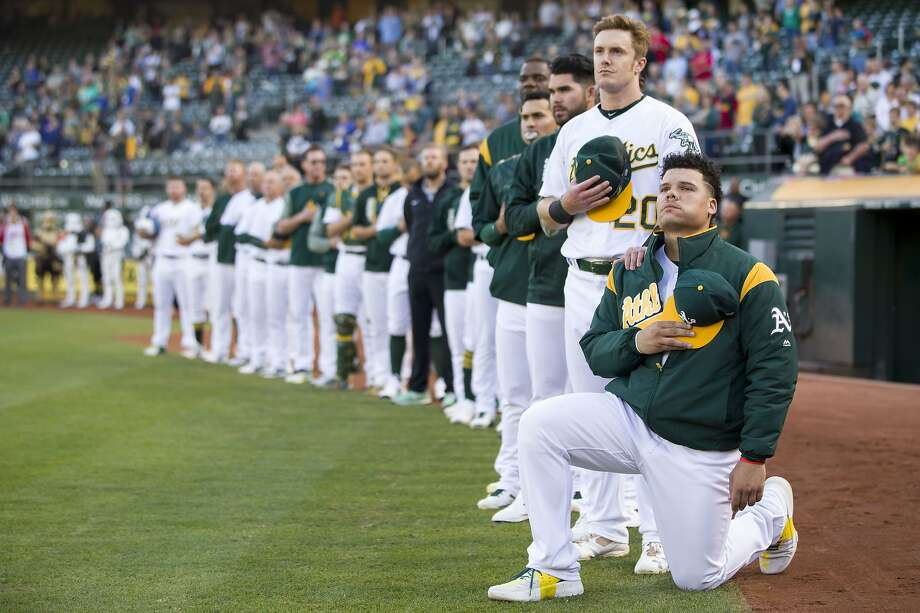Oakland Athletics catcher Bruce Maxwell (13) takes a knee as Oakland Athletics left fielder Mark Canha (20) puts his hand on his shoulder during the playing of the national anthem before an MLB baseball game between the Oakland Athletics and Texas Rangers at the Oakland Coliseum on Saturday, Sept. 23, 2017, in Oakland. Photo: Santiago Mejia, The Chronicle