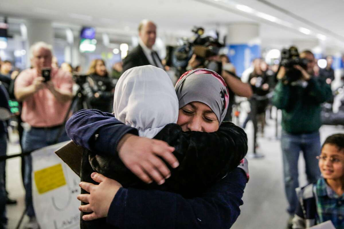 Eman Ali, (center, right), 12-year old girl from Yemen embraces her sister Salma Ali, 14 (left) after arriving at San Francisco International airport after six years of trying to obtain citizenship, in San Francisco, California, on Sunday, Feb. 5, 2017. Eman had not seen her sister Salma for three years.