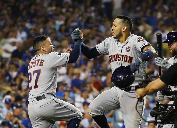 Houston Astros second baseman Jose Altuve (27) and short stop Carlos Correa celebrate their back to back home runs in the tenth inning of Game 2 of the World Series at Dodger Stadium on Wednesday, Oct. 25, 2017, in Los Angeles.