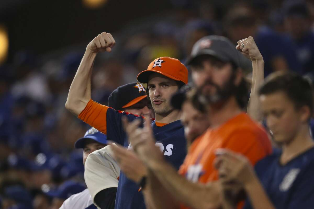 Astros fans react to George Springer's two-run home run in the eleventh inning of Game 2 of the World Series at Dodger Stadium on Wednesday, Oct. 25, 2017, in Los Angeles.