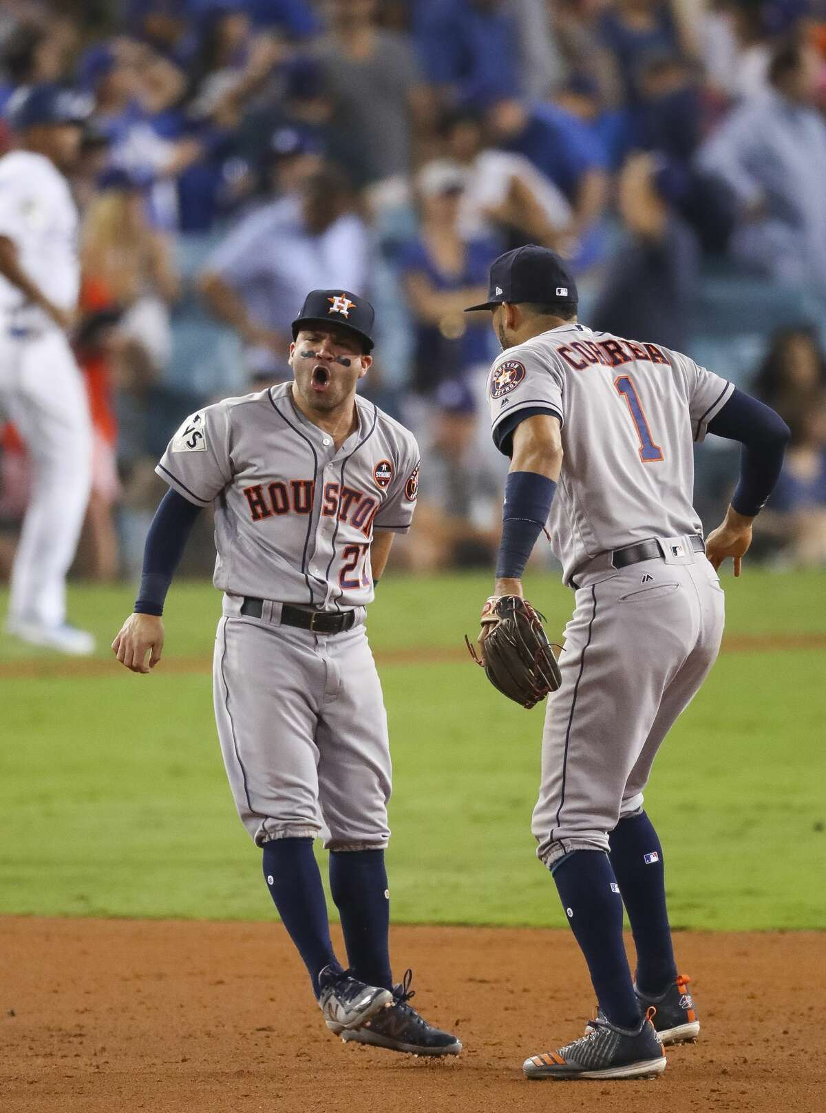 Houston Astros second baseman Jose Altuve (27) and Houston Astros shortstop Carlos Correa (1) react at the conclusion of the Astros 7-6 win in Game 2 of the World Series at Dodger Stadium on Wednesday, Oct. 25, 2017, in Los Angeles.
