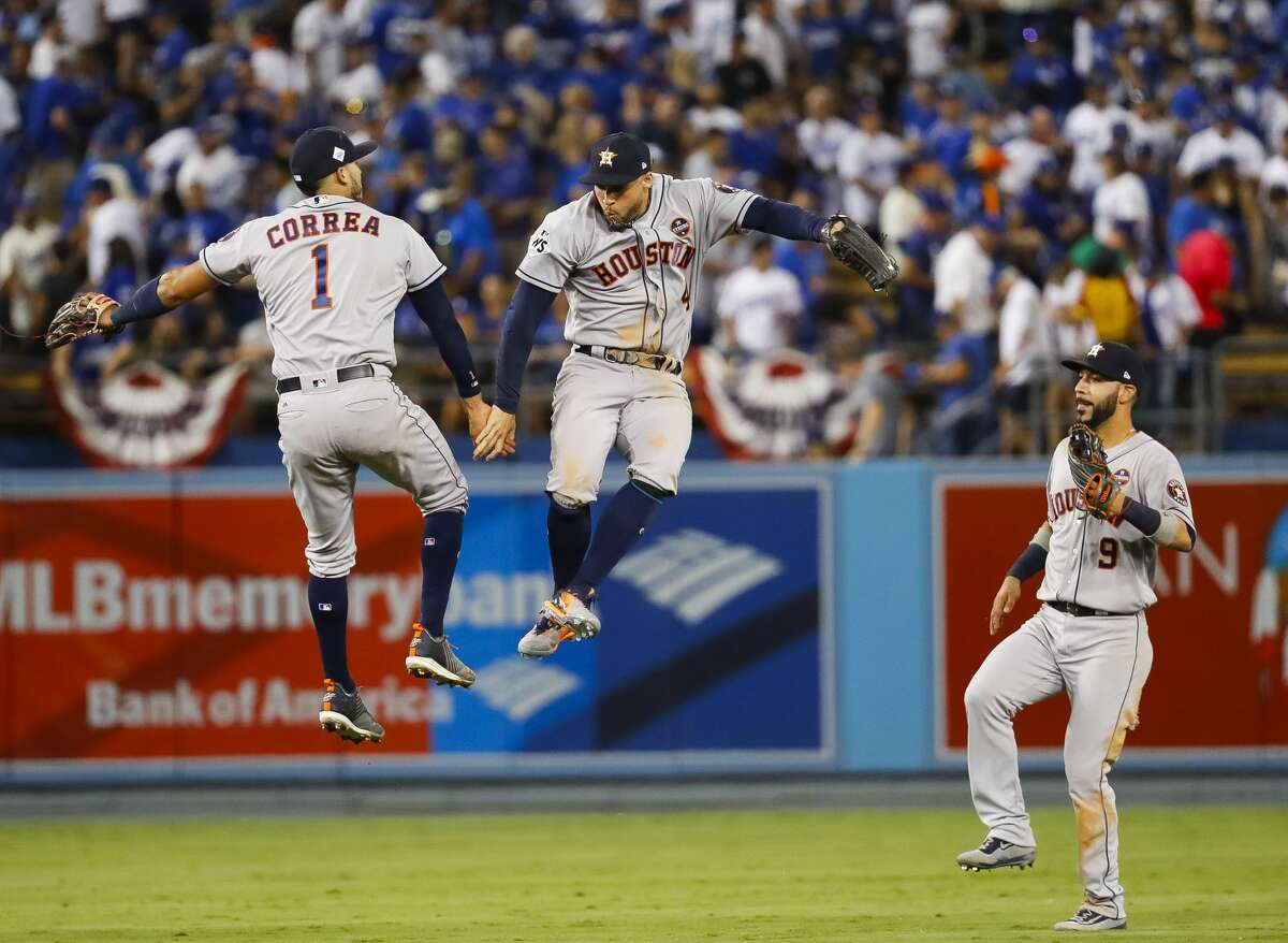 Houston Astros shortstop Carlos Correa (1) and center fielder George Springer (4) celebrate the Astros 7-6 eleventh inning win in Game 2 of the World Series at Dodger Stadium on Wednesday, Oct. 25, 2017, in Los Angeles.