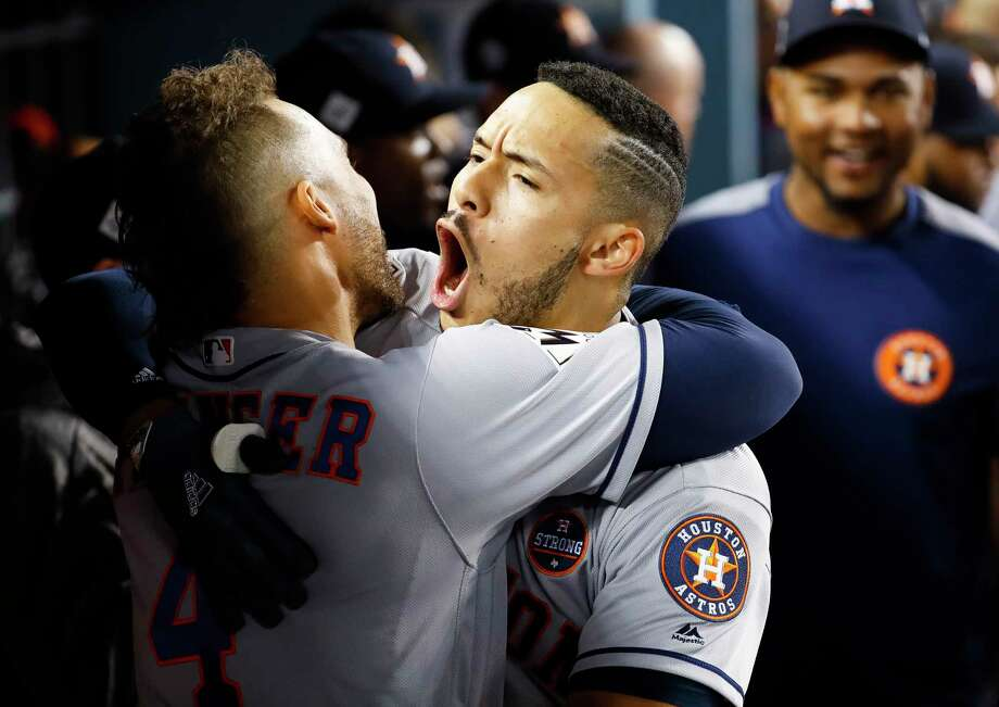 Astros center fielder George Springer, left, and shortstop Carlos Correa celebrate Correa's home run in the tenth inning of Game 2 Wednesday night. Springer's two-run shot in the 11th put the Astros ahead to stay and evened the World Series at a game apiece. Photo: Karen Warren, Houston Chronicle / © 2017 Houston Chronicle