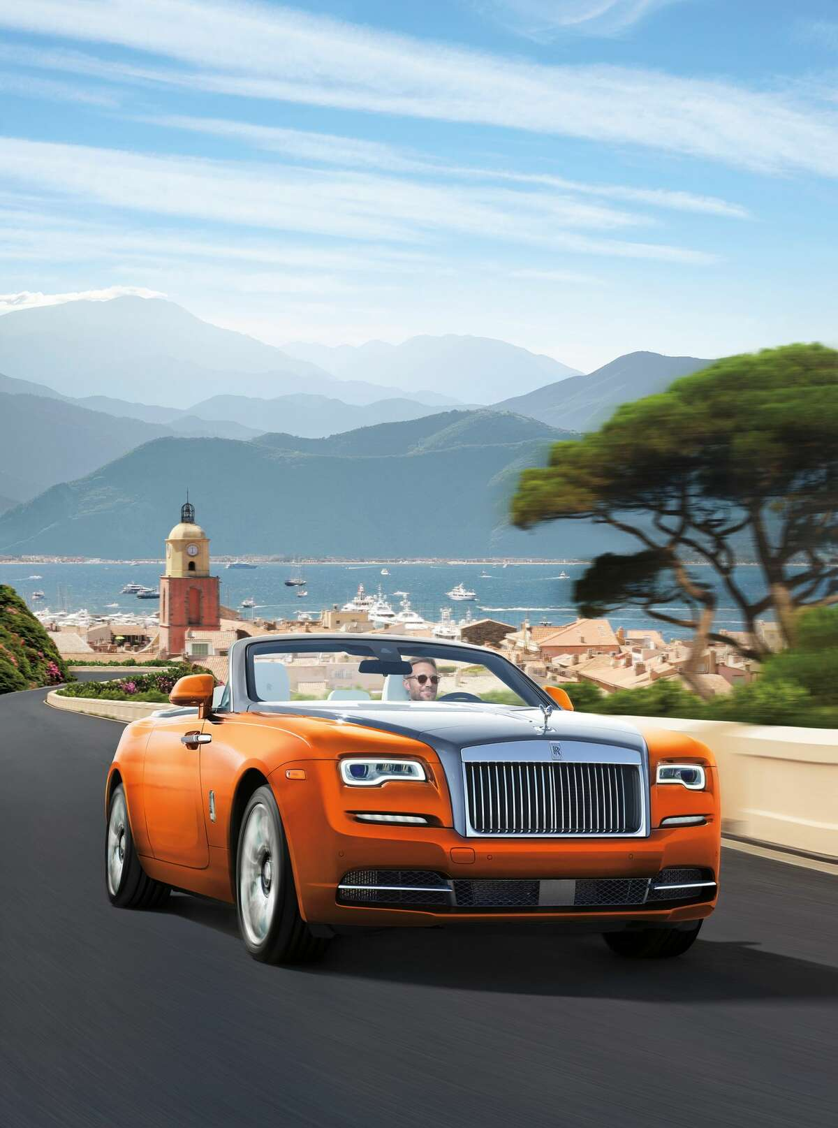 HER CAR: Rolls Royce Dawn photographed on a composited version of Saint Tropez. This V12-engined car boasts a interior of Arctic White leather, accented with dark spice brown and deep orange, with a dashboard and doors paneled in rich Canadel open-pore wood. PRICE TAG: $445,750