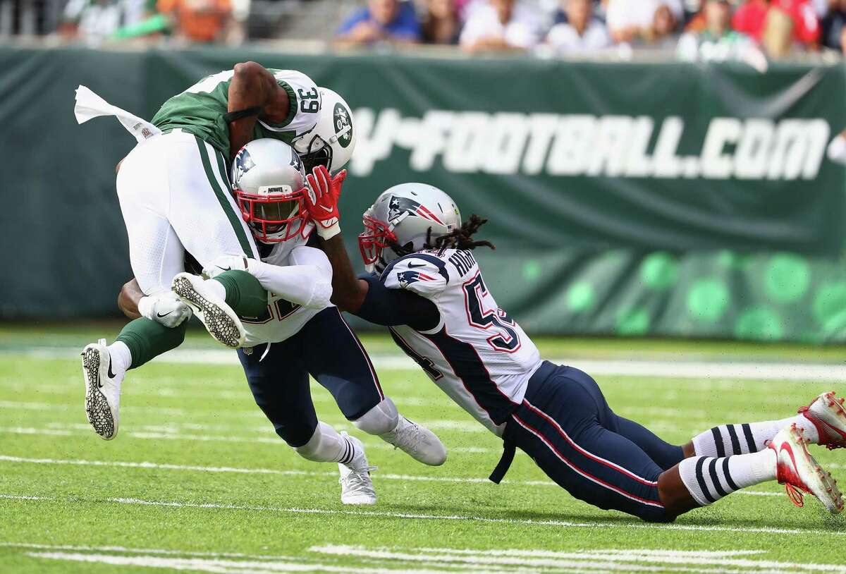 EAST RUTHERFORD, NJ - OCTOBER 15: Free safety Devin McCourty #32 and middle linebacker Dont'a Hightower #54 of the New England Patriots tackles running back Travaris Cadet #39 of the New York Jets during the second half of their game at MetLife Stadium on October 15, 2017 in East Rutherford, New Jersey.