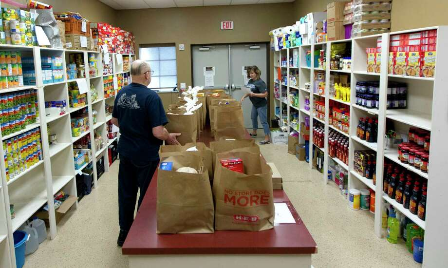 Volunteers sort bags for families at the Stonebridge Church food pantry, Thursday, in The Woodlands. The outreach program, which offers non-perishable food to families and individuals in need, was awarded $750 by the Johnson Development Corporation. Photo: Jason Fochtman, Staff Photographer / © 2017 Houston Chronicle