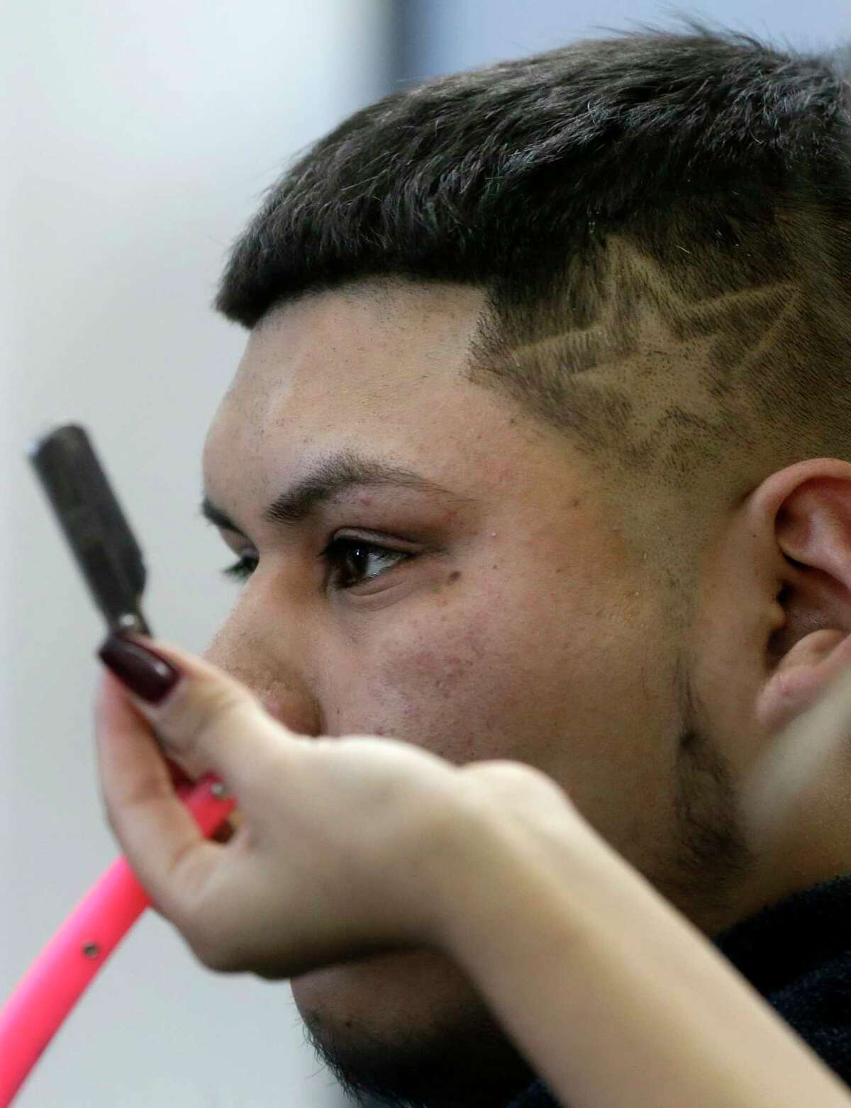 Astros fan Albert Sanchez, shown reflected in a mirror, watches as Diana Martinez, owner of Studio Cutz Beauty & Barber, 9461 Kempwood Dr., designs a star representing the Houston Astros logo into his fade haircut Wednesday, Oct. 25, 2017, in Houston.