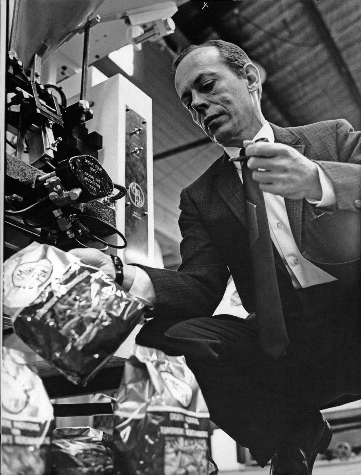 10/1965 - Inventor William C. Leasure holds a sample bag made and filled by the automatic packaging machine his company, Mira-Pak Inc., manufactures. The new method of packaging snack foods has enabled Mira-Pak to sell the machinery world-wide.