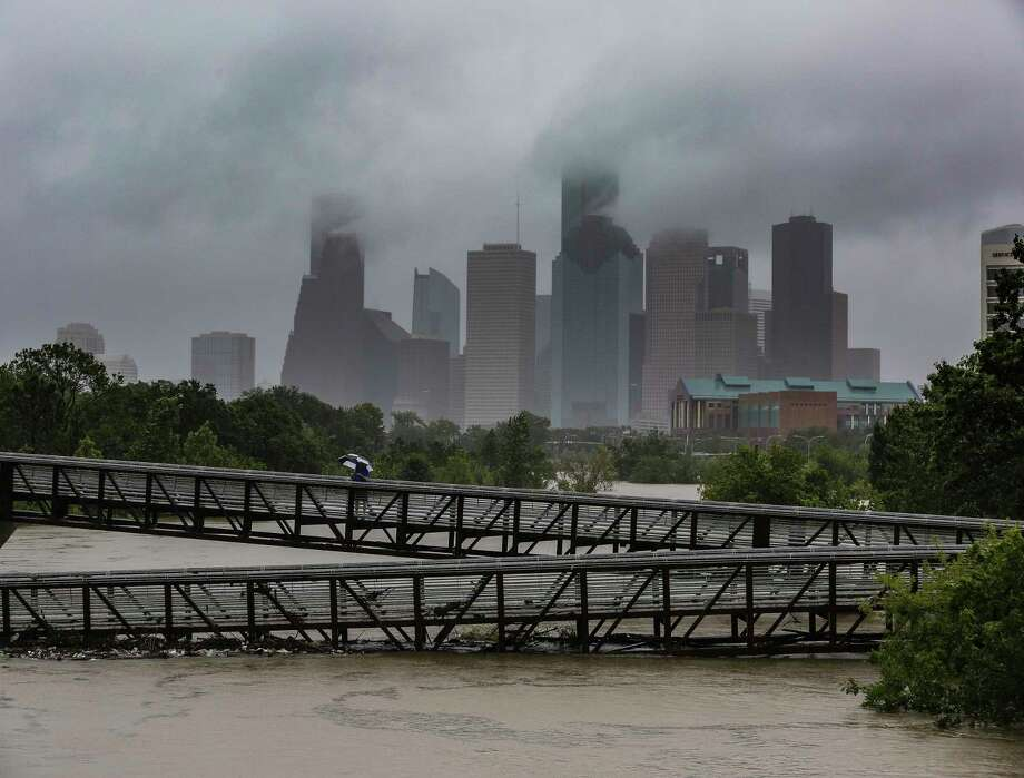 People walk over the Rosemont Pedestrian Bridge to look at a flooded Buffalo Bayou as Tropical Storm Harvey continues to dump rain over downtown Houston Tuesday, Aug. 29, 2017. Photo: Michael Ciaglo, Houston Chronicle / Michael Ciaglo