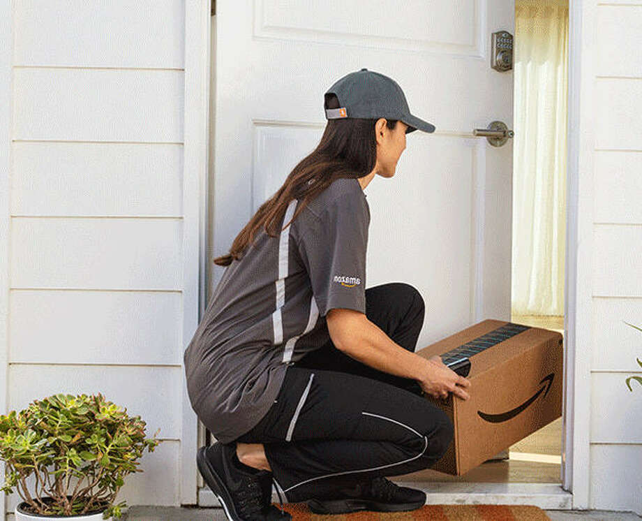 A delivery person places a package inside a customer's home using Amazon Key.
