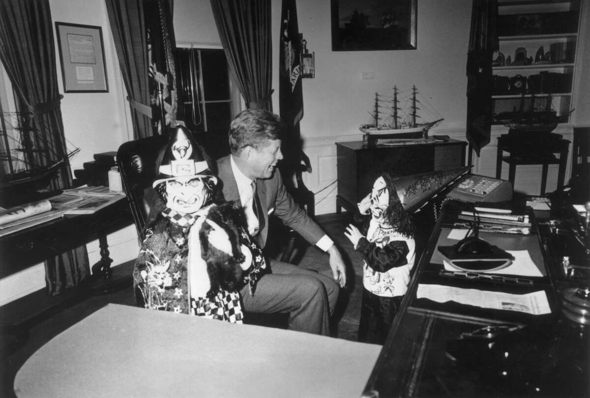 1963: US President John F Kennedy sits behind his desk, laughing as his children Caroline and John Jr., show him their Halloween costumes in the Oval Office of the White House, Washington, DC. They wear plastic hats and fright masks.