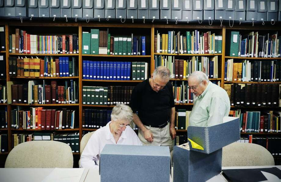 Volunteers Marilyn Penfield, Ron Marcus and Hank Silverstein work in the library at the Stamford Historical Society in Stamford, Conn. on Friday June 25, 2010.  Due to budget cuts, the library will go from being open five days a week to three after July 1. Photo: Kathleen O'Rourke / Stamford Advocate