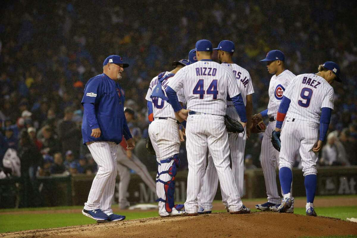 Chicago Cubs pitching coach Chris Bosio, left, talks to Carl Edwards Jr. as players gather on the pitching mound during the eighth inning of Game 4 of baseball's National League Division Series against the Washington Nationals, Wednesday, Oct. 11, 2017, in Chicago. (AP Photo/Nam Y. Huh)