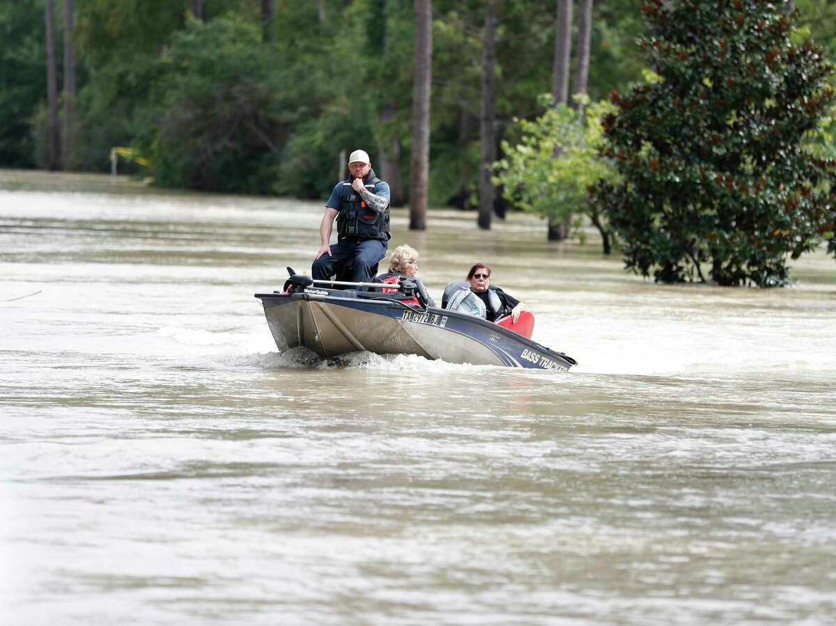 A woman is brought in to a high spot on the bridge at West Lake Houston Parkway, as floodwaters overflowed from the San Jacinto River from Tropical Storm Harvey, Wednesday, Aug. 30, 2017, in Kingwood. ( Karen Warren / Houston Chronicle )