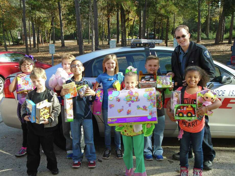 Conroe ISD officer Steven Esch stands with children donating unwrapped toys at Hailey Elementary during the 2016 Children in Santa's Dreams toy drive. Photo: Contributed Photo / Copyright 2009